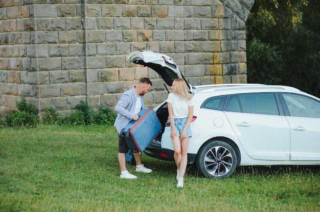 Retrato de família feliz. férias, viagens - família pronta para viajar nas férias de verão. malas e rota do carro.