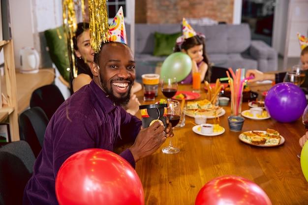 Retrato de família feliz multiétnica, comemorando um aniversário em casa. grande família comendo lanches e bebendo vinho, enquanto cumprimenta e se diverte as crianças. comemoração, família, festa, conceito de casa.