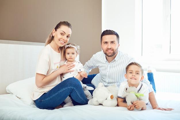 Retrato de família feliz na cama no quarto