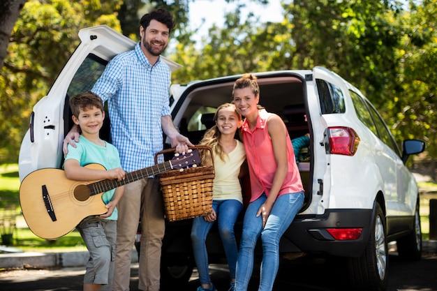 Retrato de família feliz perto de carro