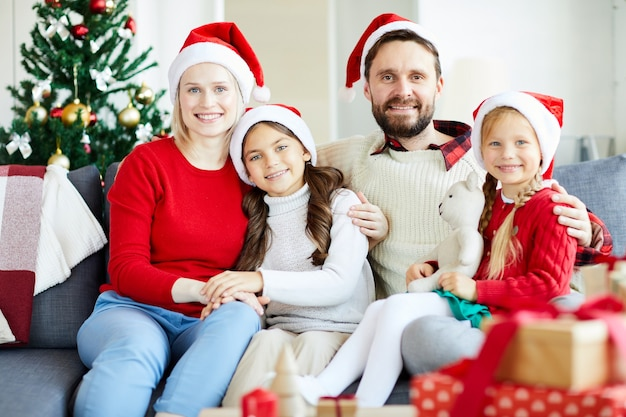 Retrato de família feliz sentado no sofá com chapéus de papai noel