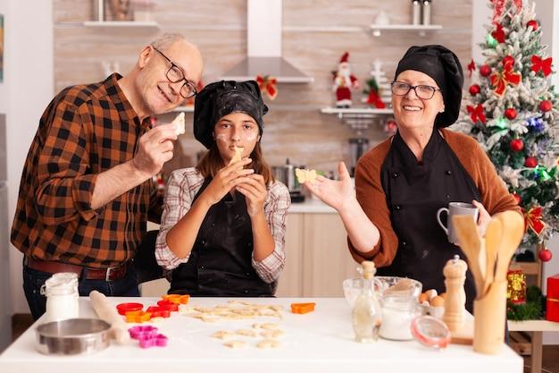 Retrato de família feliz usando avental segurando massa de biscoitos caseiros