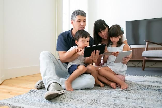 Retrato de família feliz usando tablet e smartphone.