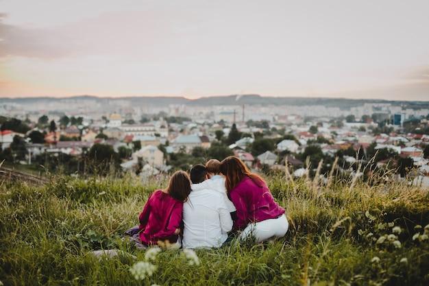 Retrato de família. homem, duas mulheres e um menino sentam na grama