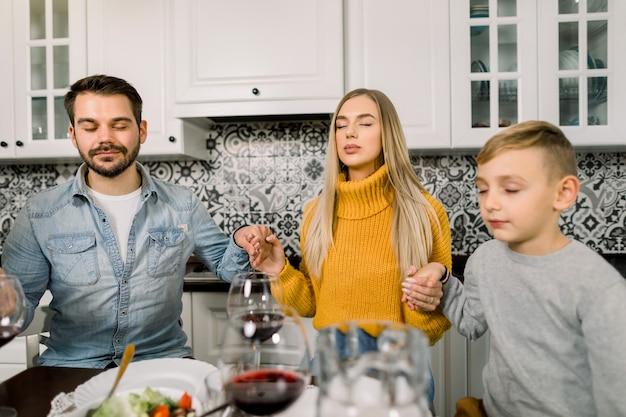 Retrato de família jovem moderna, pai, mãe e filho, sentado à mesa festiva e rezar.