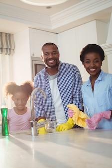 Retrato de família lavar utensílios na pia da cozinha