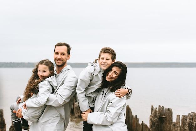 Retrato de família linda vestida de capa de chuva perto do mar
