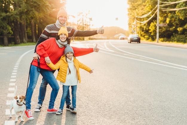Retrato de família: mãe, pai e filha andar com animal de estimação, ficar na estrada