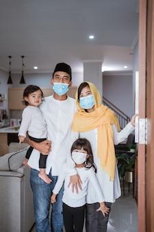 Retrato de família muçulmana com máscara em frente à porta da casa dando as boas-vindas aos hóspedes durante a celebração do eid mubarak