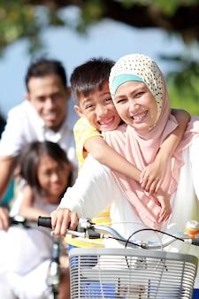 Retrato de família muçulmana feliz andando de bicicleta juntos