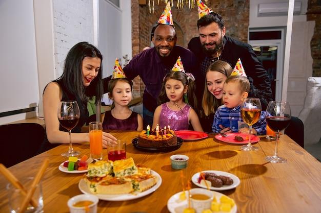 Retrato de família multiétnica feliz comemorando aniversário em casa