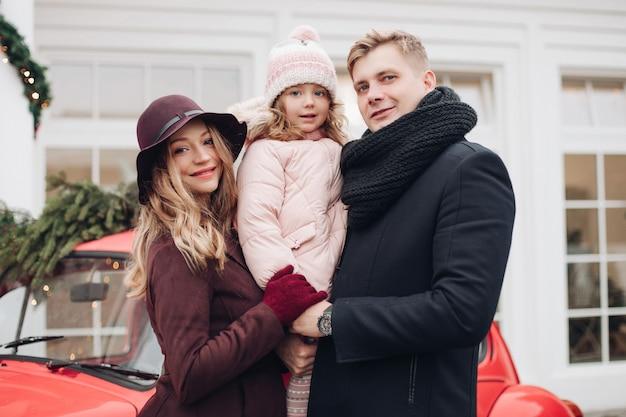 Retrato de família na moda sorridente posando ao ar livre juntos, rodeado por neve e abeto