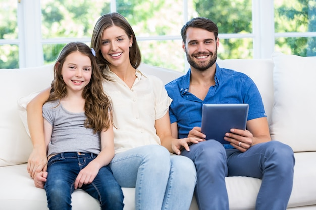 Retrato de família sentada no sofá com tablet digital