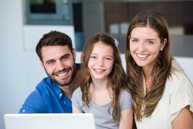 Retrato de família sorridente com laptop