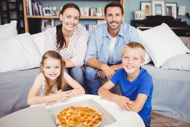 Retrato de família sorridente com pizza