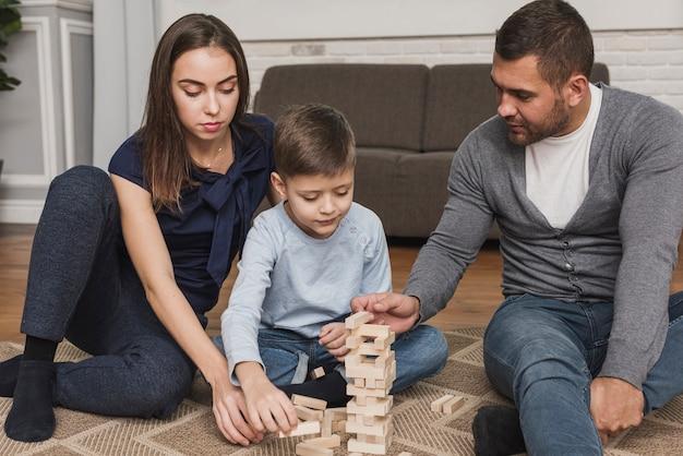 Retrato de família tocando jenga juntos