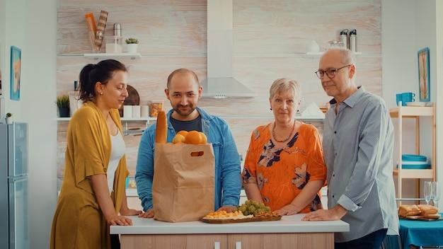 Retrato de família vídeo em câmera lenta sentado na cozinha moderna. pessoas felizes sorrindo para a câmera na sala de jantar ao redor da sacola de papel com mantimentos olhando para a câmera