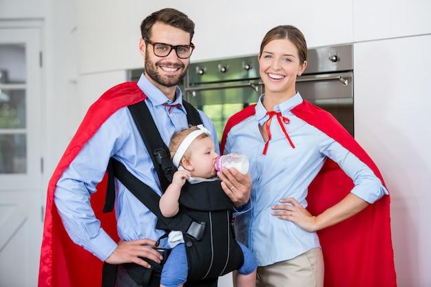 Retrato de fantasia de casal, alimentação de leite para a filha em casa