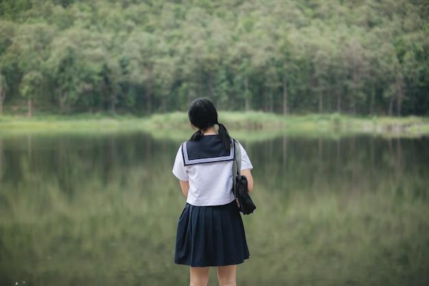 Retrato de fantasia de menina da escola japonesa asiática, olhando para o estilo vintage de filme ao ar livre do parque