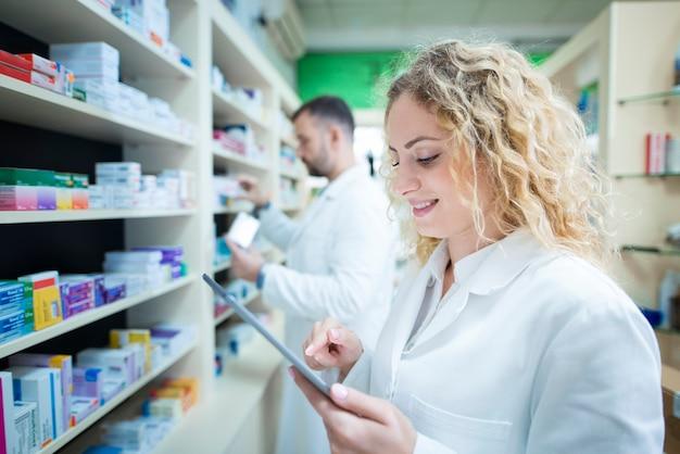 Retrato de farmacêutico alegre com comprimido em pé na farmácia enquanto farmacêutico masculino, realocando o medicamento na prateleira.