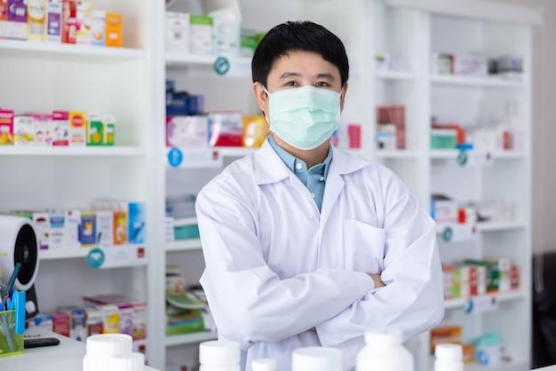Retrato de farmacêutico masculino asiático em pé abraço e máscara protetora em farmácia na tailândia