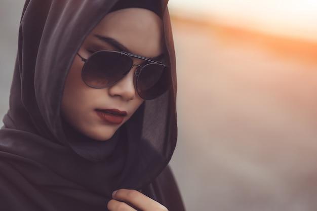 Retrato de fashi da bela jovem muçulmana com o hijab preto e óculos de sol. estilo vintage