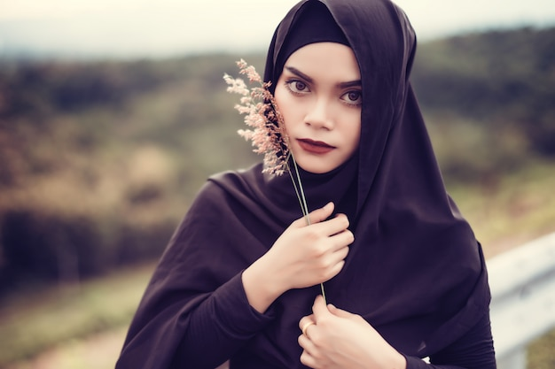 Retrato de fashi da jovem mulher muçulmana bonita com o hijab preto. mulher muçulmana segurando flor de grama. estilo vintage