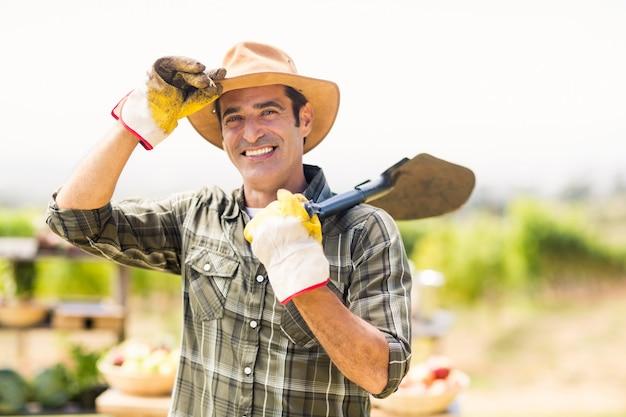 Retrato de fazendeiro carregando pá