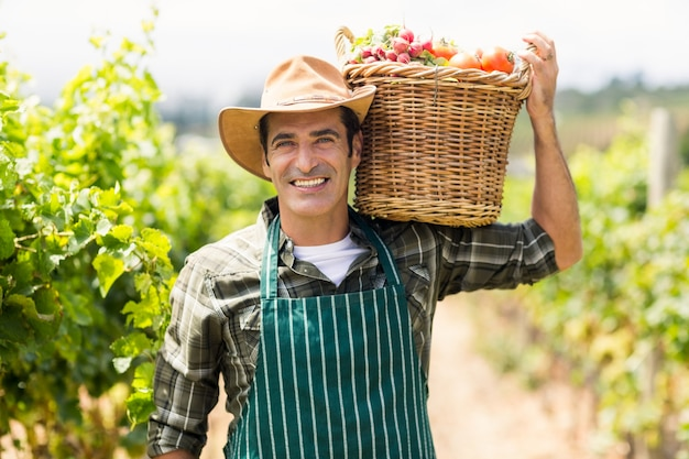 Retrato de fazendeiro feliz carregando uma cesta de legumes