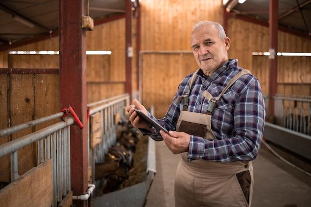 Retrato de fazendeiro sênior com computador tablet, verificando o abastecimento de comida e cuidando de animais domésticos na casa de fazenda