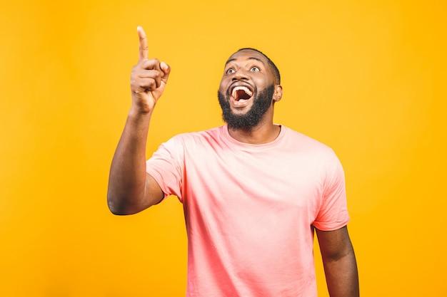 Retrato de feliz afro-americano jovem bonito com casual sorrindo, apontando de lado com o dedo, olhando com expressão de rosto animado