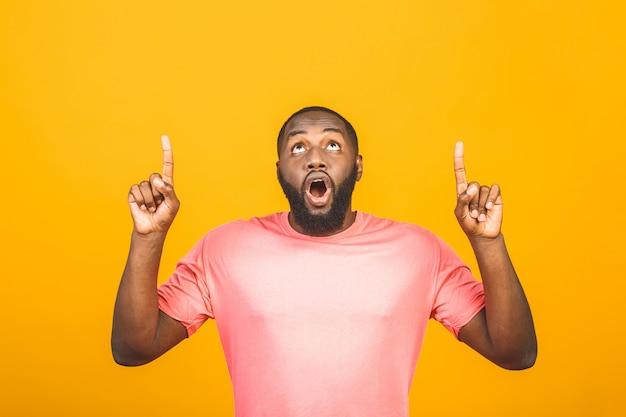 Retrato de feliz afro-americano jovem bonito com casual sorrindo, apontando para o lado com o dedo