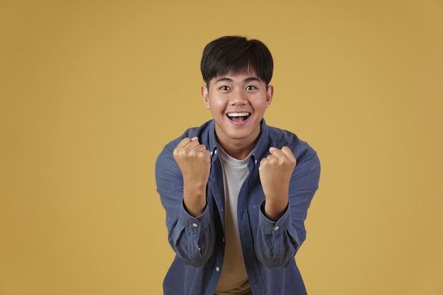 Retrato de feliz alegre feliz regozijando-se animado muito jovem asiático vestido casualmente isolado