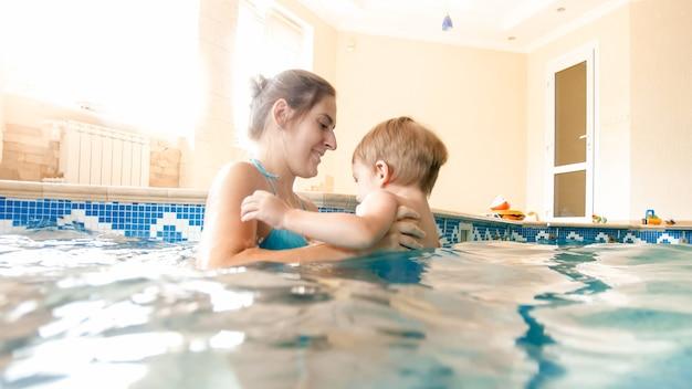Retrato de feliz alegre jovem mariposa com menino de 3 anos de idade criança brincando na piscina em casa. criança aprendendo a nadar com os pais. família se divertindo no verão