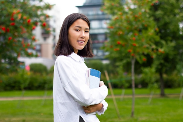Retrato de feliz alegre menina asiática na universidade