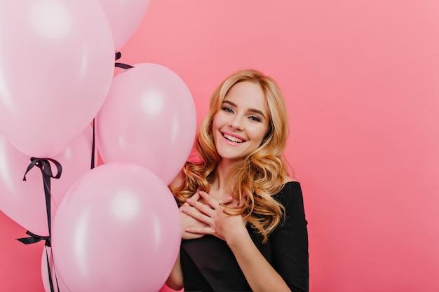 Retrato de feliz aniversariante branca. mulher loira entusiasmada em um traje preto, esperando a festa e rindo.