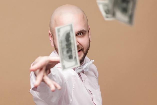 Retrato de feliz bonito meio envelhecido careca barbudo empresário em pé de camisa branca, jogar fora dinheiro e olhando para a câmera com orgulhoso rosto rico. tiro do estúdio, isolado em fundo marrom claro.
