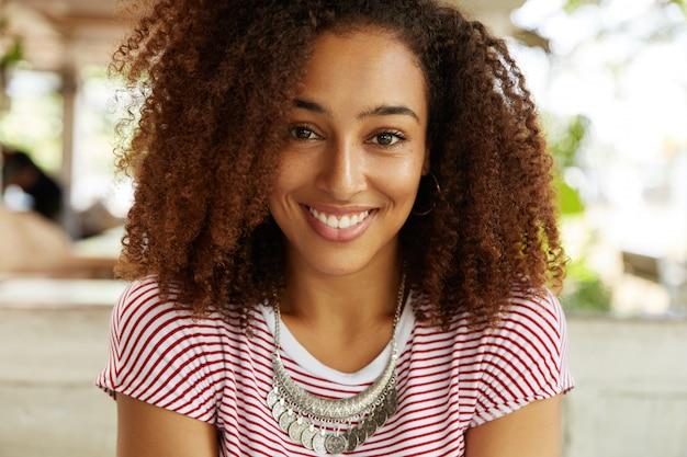 Retrato de feliz de mulher de pele escura com penteado afro espesso encaracolado, descansa em um café