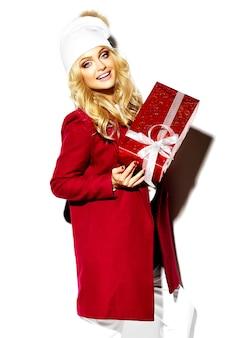 Retrato de feliz doce sorridente mulher loira bonita segurando nas mãos dela grande caixa de presente de natal em roupas de inverno casual vermelho hipster