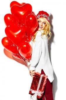 Retrato de feliz doce sorridente mulher loira linda segurando nas mãos dela grande caixa de presente de natal e balões de coração em roupas de inverno casual hipster vermelho, em camisola quente branca