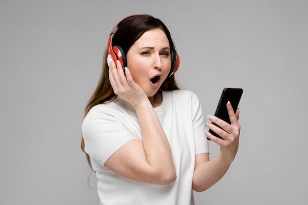 Retrato de feliz emocional bonito mais o modelo de tamanho em fones de ouvido, olhando na câmera, segurando o telefone móvel, ouvindo música
