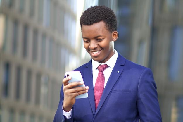 Retrato de feliz empresário bonito positivo, jovem negro afro-americano, homem afro-americano olhando para a tela do seu celular e sorrindo. boas notícias. tecnologia, negócios, conceito de smartphone.