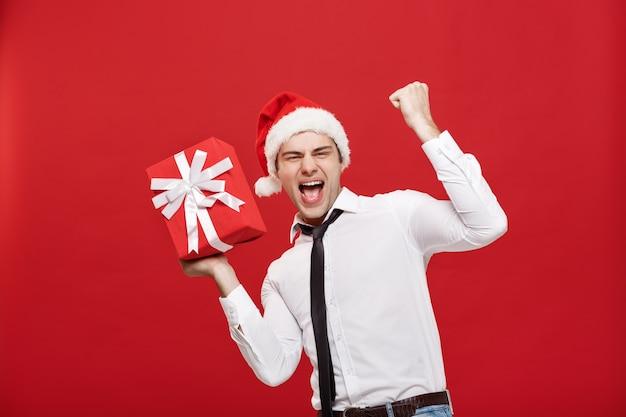 Retrato de feliz empresário de natal de santa, excitante com seu presente sobre fundo vermelho.