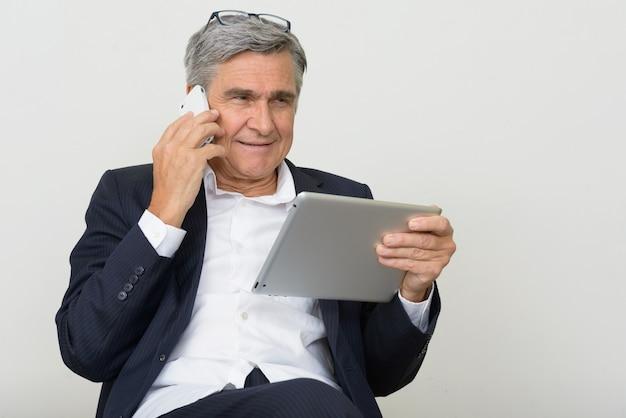 Retrato de feliz empresário sênior usando telefone e tablet digital