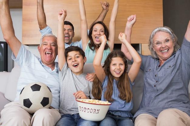 Retrato de feliz família ampliada assistindo tv na sala de estar