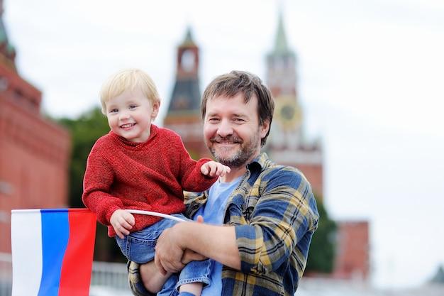 Retrato, de, feliz, família, com, bandeira russa, com, kremlin moscow