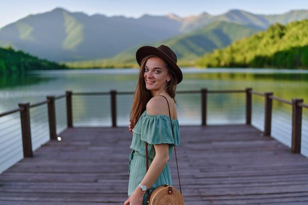 Retrato de feliz fofo sorridente atraente viajante garota usando chapéu e vestido verde sozinho no cais com vista para o lago e as montanhas. desfrutando de uma atmosfera serena tranquila e pacífica na natureza