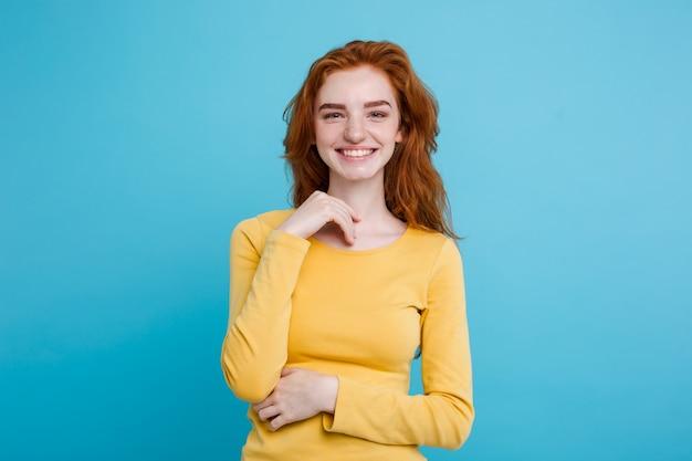 Retrato de feliz gengibre menina de cabelo vermelho com sardas sorrindo olhando câmera. fundo azul pastel. espaço de cópia.