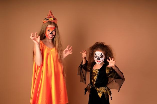 Retrato de feliz halloween de crianças fantasiadas em uma parede bege
