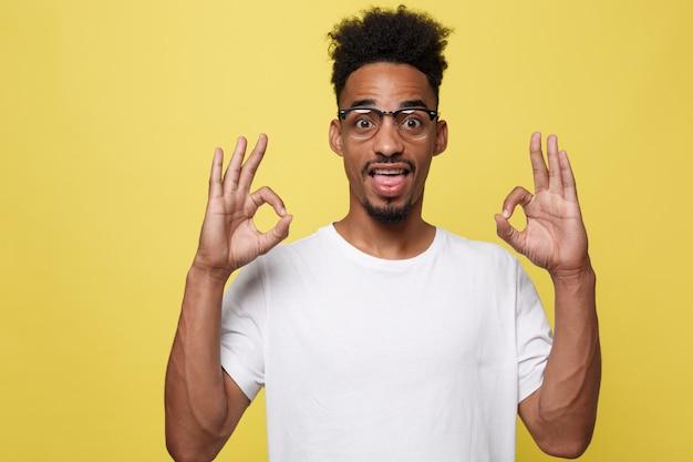 Retrato, de, feliz, homem africano-americano, mostrando, tá bom sinal, e, sorrindo